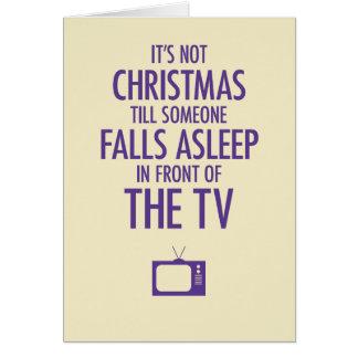 El caer dormido delante de la tarjeta de Navidad