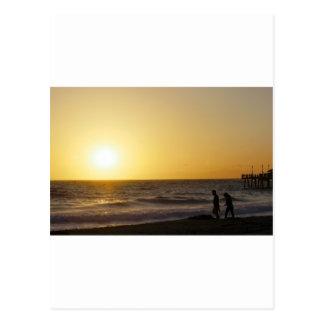 El caminar en la puesta del sol postal