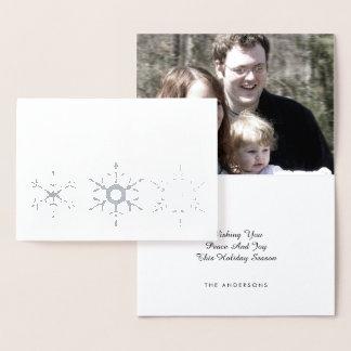 El copo de nieve de plata de la paz y de la tarjeta con relieve metalizado