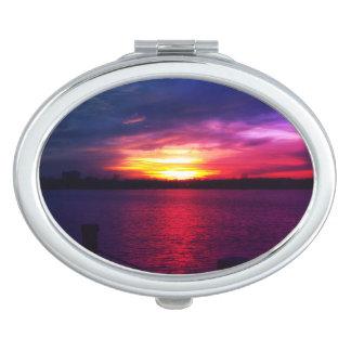 El espejo compacto de la puesta del sol de las