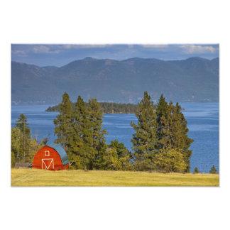 El granero rojo se sienta a lo largo del lago de c arte fotográfico