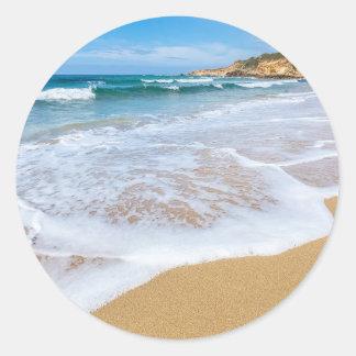 El mar de la playa de Sandy agita y montaña en la Pegatina Redonda