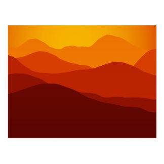 El naranja entona puesta del sol sobre siluetas de postal