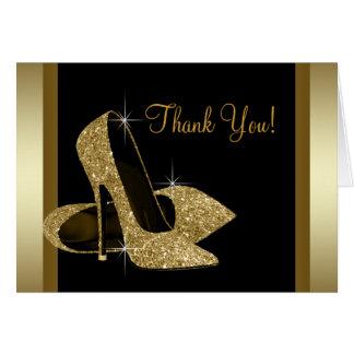 El negro y el zapato del tacón alto del oro le tarjeta