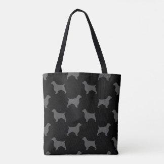 El perro de aguas de saltador galés siluetea el bolso de tela