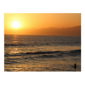 El practicar surf en la puesta del sol en la playa postal