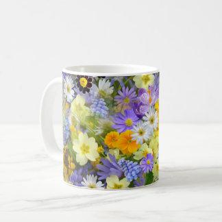 El prado hermoso de la primavera florece la taza