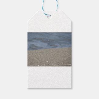 El primer de la playa de la arena con el mar etiquetas para regalos