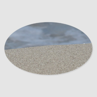 El primer de la playa de la arena con el mar pegatina ovalada