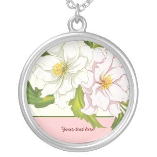 El ramo de flores rosadas y blancas platea el colgante redondo