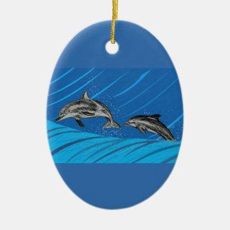 El saltar de los delfínes del mar adorno navideño ovalado de cerámica