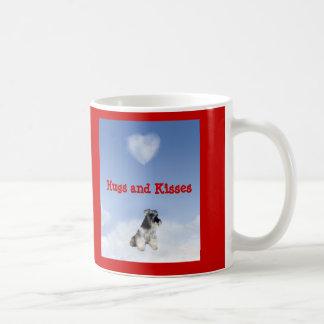 El Schnauzer miniatura abraza y besa la taza