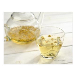 El té de hierba que una tetera de cristal y una postal