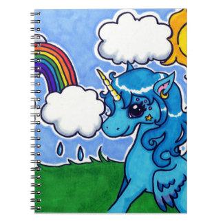 El unicornio azul que vuela con espiral del arco i libro de apuntes con espiral