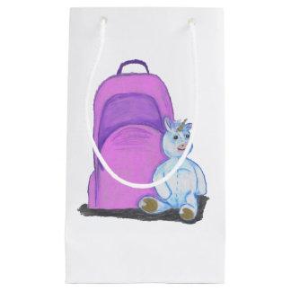 El unicornio relleno se sienta por una mochila bolsa de regalo pequeña