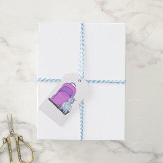 El unicornio relleno se sienta por una mochila etiquetas para regalos