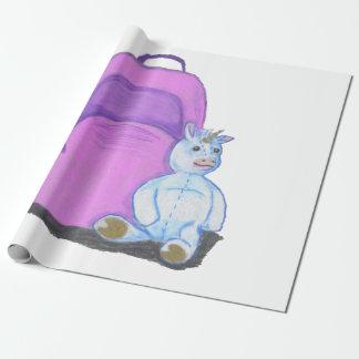 El unicornio relleno se sienta por una mochila papel de regalo