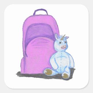 El unicornio relleno se sienta por una mochila pegatina cuadrada