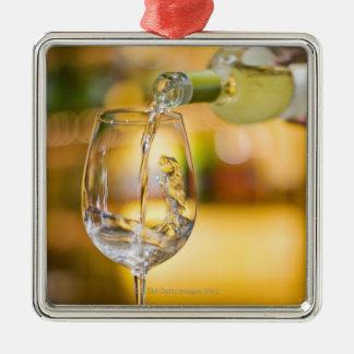 El vino blanco se vierte de la botella en adorno cuadrado plateado