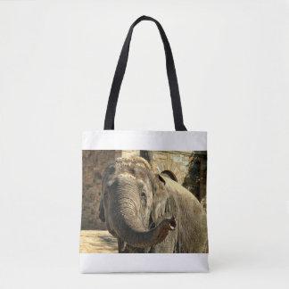 Elefante que señala adelante con el tronco bolso de tela