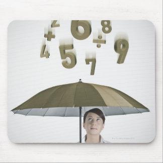 Empresaria debajo del paraguas con números y alfombrilla de ratón
