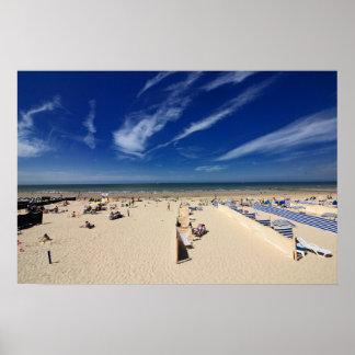 En la playa, cielo azul póster