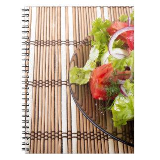 Ensalada vegetariana de verduras frescas en un cuaderno
