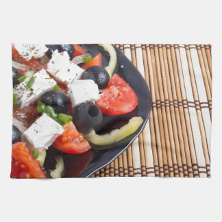 Ensalada vegetariana fresca en una placa negra en toallas de mano