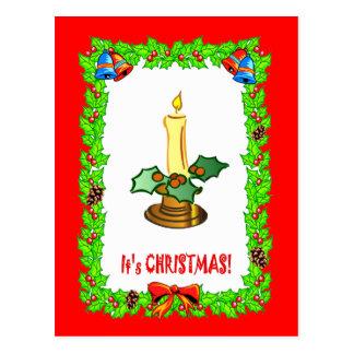 Es navidad, vela y decoraciones postal