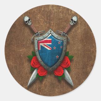 Escudo y espadas envejecidos de la bandera de etiqueta redonda
