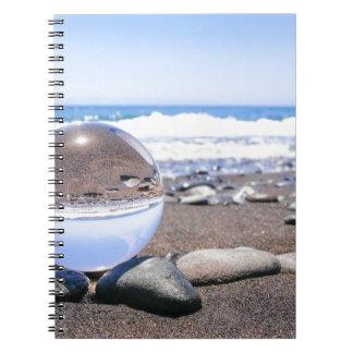Esfera de cristal en piedras en la playa y la cuaderno