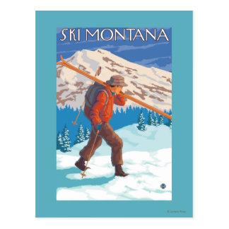 Esquís de la nieve del esquiador que llevan - postal