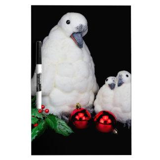 Estatuillas del pingüino como familia con las pizarra blanca