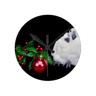 Estatuillas del pingüino con la bola roja del reloj redondo mediano