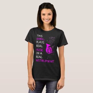 Este chica juega la trompa real del instrumento de camiseta