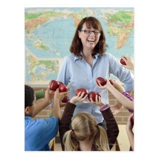 estudiantes jovenes que presentan manzanas al prof tarjeta postal