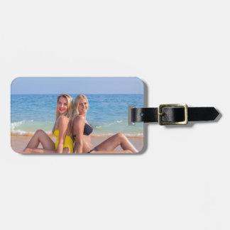 Etiqueta Para Maletas Dos chicas se sientan en la playa cerca de sea.JPG