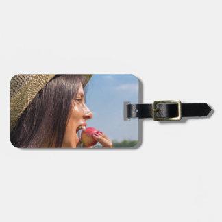 Etiqueta Para Maletas Mujer con el gorra que come la manzana roja afuera
