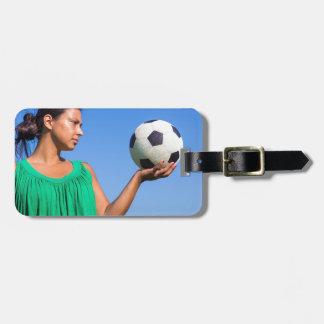 Etiqueta Para Maletas Mujer joven que lleva a cabo fútbol en la mano con