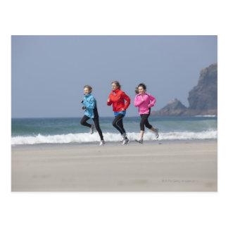 Familia que corre junto en la playa postal