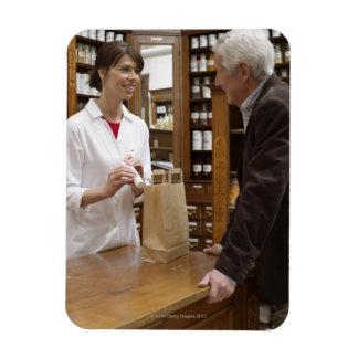 Farmacéutico de sexo femenino que aconseja a clien iman de vinilo