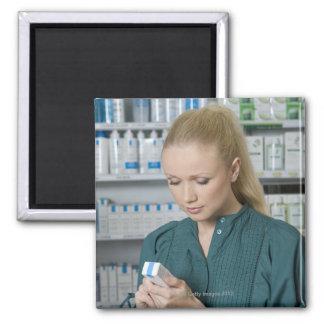 Farmacéutico de sexo femenino que mira la medicina iman para frigorífico