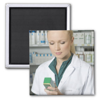 Farmacéutico de sexo femenino que mira la medicina iman de nevera