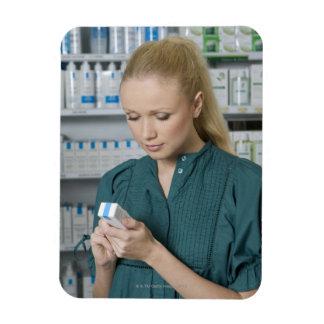 Farmacéutico de sexo femenino que mira la medicina iman rectangular