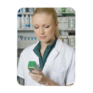 Farmacéutico de sexo femenino que mira la medicina imán