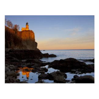 Faro partido de la roca en la puesta del sol cerca postal