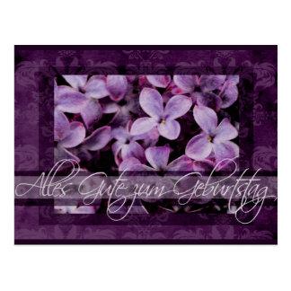 Feliz cumpleaños en flores alemanes de la lila postal