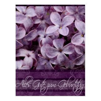 Feliz cumpleaños en flores alemanes de la lila tarjeta postal