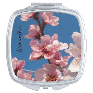 Flores rosadas con el cielo azul en sping espejo para el bolso