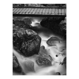 Foto Puente de madera y agua móvil en el bosque
